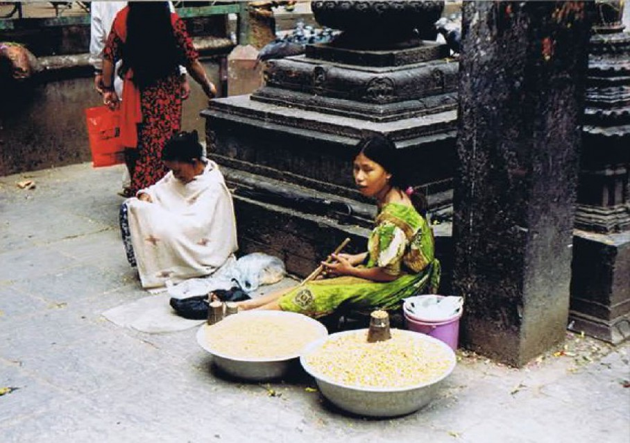 Lady selling yellow rice used at sacred rituals...